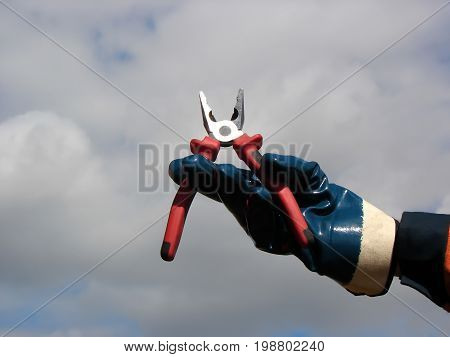 Hand with protective glove holding the pliers open against the sky.