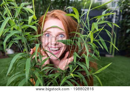 Beautiful red-haired woman is enjoying forward to her garden