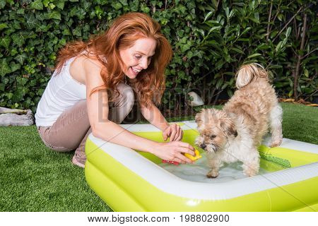 Beautiful red-haired woman plays with her dog by the pool