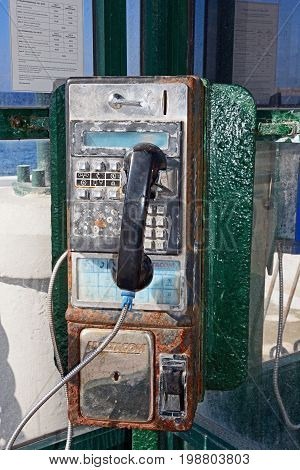 BUGIBBA, MALTA - MARCH 28, 2017 - Rusty old public pay phone in a phone booth Bugibba Malta Europe, March 28, 2017.