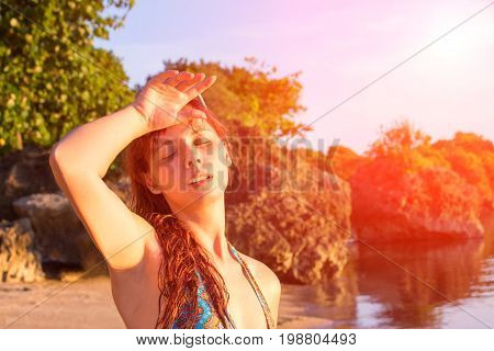 Sunstroke on hot beach. Young woman with heatstroke. Health problem on vacation. Medicine on vacation. Dangerous sun. Beach life. Girl under sun. Red hair girl on beach by sea. Holiday health care