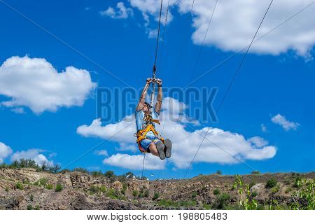 Ukraine Migea - July 30 2017: Zipline. A view of a man sliding on a steel cable against a beautiful blue sky with white clouds. Extreme and active rest.