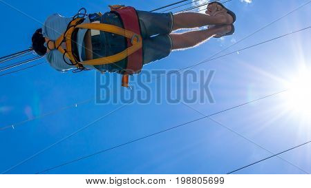 Zipline. A view of a man sliding on a steel cable against a beautiful blue sky with white clouds. Extreme and active rest.