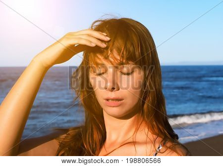 Young woman with heatstroke. Health problem on vacation. Medicine on vacation. Dangerous sun. Beach life. Sunstroke on hot beach. Girl under sun. Red hair girl on beach by sea. Holiday health care