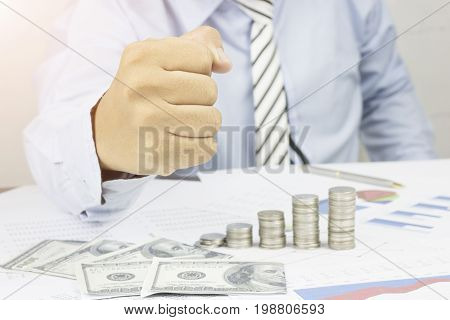 Businessman show fist to certain and success in business on table with money work paper and coins concept as be certain confident in finance and banking