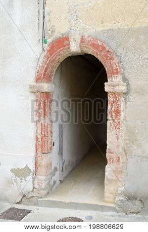 Small passage under a house with a porch in stone arch of France in the town of Bar le Duc in the department of Meuse in France