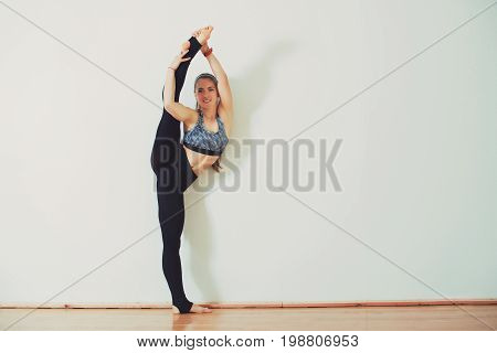 Smiling Young Woman Athlete Standing In The Split In Studio.