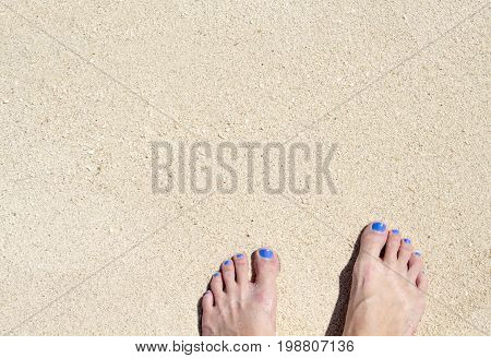 Woman feet on white beach sand. White sand top view photo for background. Sunny day by sea on exotic island concept. White sand texture with bare foot banner template. Tropical island beach surface