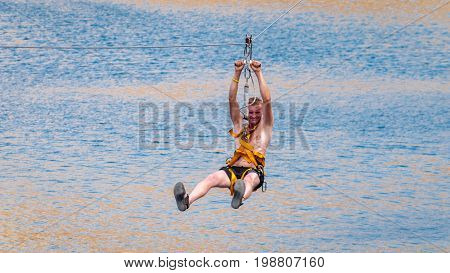 Ukraine Migea - July 30 2017: Zipline. The man in the equipment slides on a steel cable. Trolley Track Over the lake. Extreme and active rest.