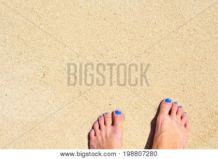 Woman feet on seashore sand. White sand beach top view photo for background. Sunny day by sea on exotic island concept. White sand texture with bare foot banner template. Tropical island beach surface
