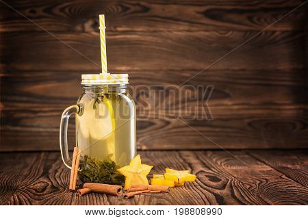 A composition of a mason jar of green tea with a lemon slice and yellow straw on a wooden background. Cinnamon sticks and stars of carambola near the hot lemon tea. Copy space.
