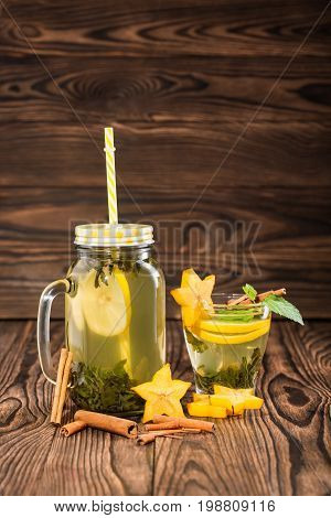 Composition of mason jar of lemon tea with yellow straw and a cup of green tea with mint and tropical carambola on a light wooden background. Healthy homemade tea with cinnamon and fruits. Copy space.