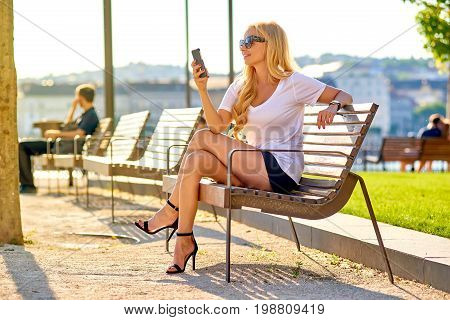 A beautiful young blond women sitting on a bench in the sunset and using her smartphone