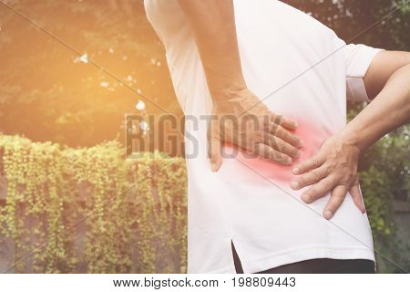 A man suffering from backache spinal injury and muscle issue problem at outdoor.