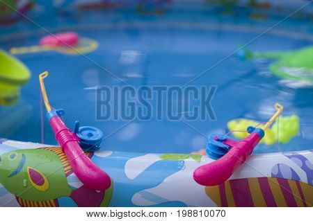 Children's game of fishing in a small pool in a private house