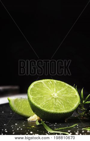 A close-up picture of fresh juicy lime on a black background. Half of fresh light green lime. Ripe, juicy, fresh, bright slice of lime with tarragon herbs. Copy space.