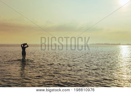young pretty woman at sunrise in the lake water