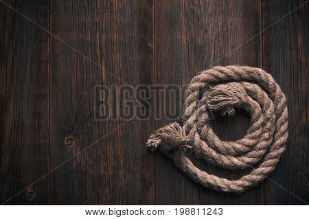 Twisted rope on a wooden background. Folded rope on the wooden floor.