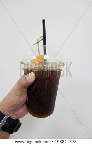 Black coffee with peach (Fusion drink) in young hand