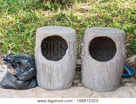 Double concrete bin which look like the stump and the garbage bag near the pavement in in the national park.