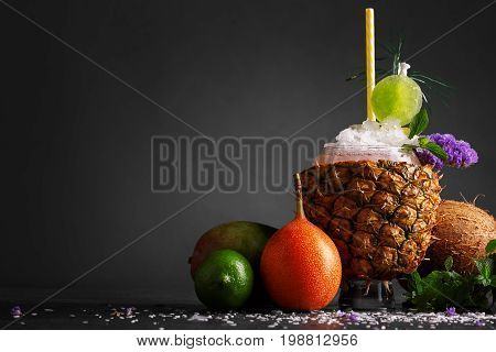 Various tropical colorful fruits on a saturated black background. A big pineapple cup full of a non-alcohol cocktail with ice, mint, and straw. Ripe mango, orange, and lime near the beverage.