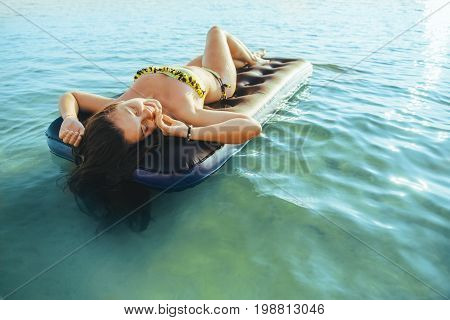 young pretty woman in bikini get suntan on inflatable mattress in the middle of the lake