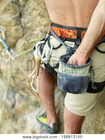 adult man rock climber. rock climber climbs on a rocky wall. harness and chalk bag close up, focus on the chalk bag and hand