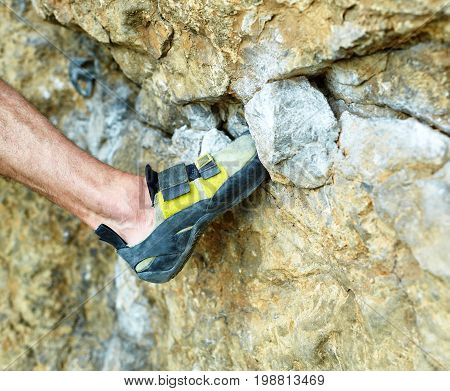 adult man rock climber. rock climber climbs on a rocky wall. Man in shorts, legs and climbing shoes close up