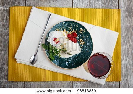 A view from above on a cold creamy snack.  A blue bowl of a milky ice cream, rustic raspberries, spicy mint and metal spoon. An icecream with a grape juice on a yellow fabric background.