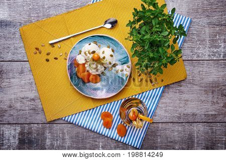A top view of a cold ice cream with dried apricots, physalis and pumpkin seeds on a yellow cloth and on a wooden background. A glass of green tea with straw near the dessert. A pot with a green plant.