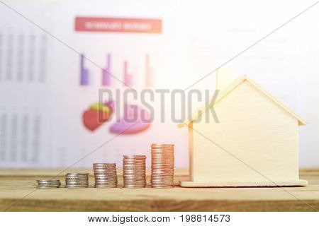 pile of coins home concept in buying selling and mortgage house finance on wood table