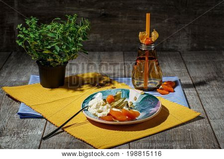 Refreshing ice cream with dried apricots, physalis and pumpkin seeds on a yellow fabric and on a wooden background. A glass of green tea with straw near the dessert. A clay pot with a green plant.