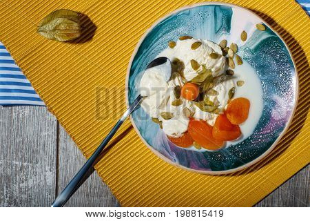 A fresh dessert with dried apricots, physalis on a yellow cloth and on a wooden background, top view. Tasty ice cream with pumpkin seeds on a blue plate. A tea spoon near the frozen yogurt.