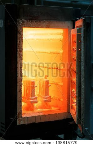 A light orange heated furnace for melting and roasting on a dark background. Professional manufacturing constructions. The dangerous process of making steel and metal.