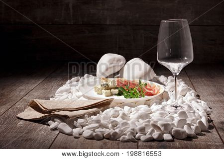 A spectacular composition of a wineglass and restaurant dinner on a plate on a heap of white rocks. Leaves, balyk and cheese with a handkerchief on a dark wooden table background.