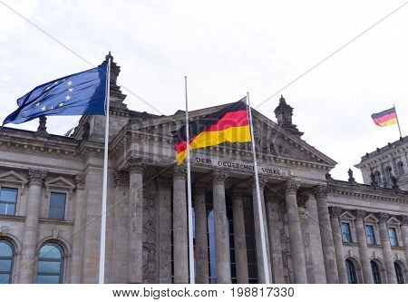 BERLIN GERMANY - AUGUST 4 2017: Germany Politics Concept: German Flag And EU Flag In Front of The Reichstag Building