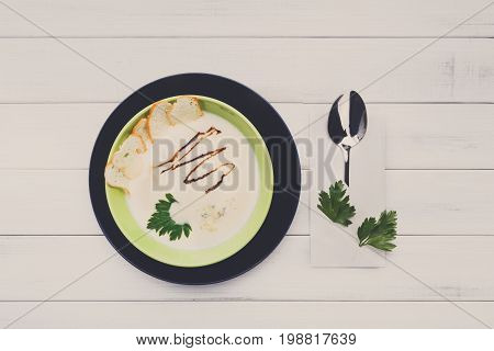 Creamy mushroom soup with croutons top view, french cuisine restaurant food on white wooden background, copy space