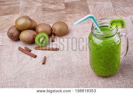 A big mason jar full of organic drink from ripe kiwi with a colorful straw and a slice of fruit on a top on a wooden background. A heap of whole and cut kiwi and cinnamon on a white tablecloth.