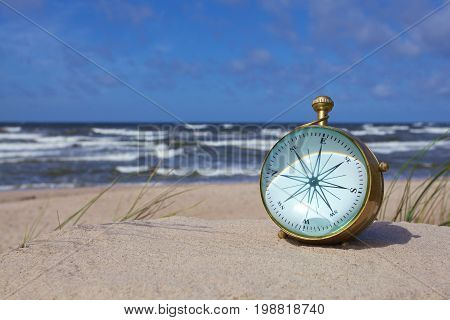 antique brass nautical compass on the beach.vintage style