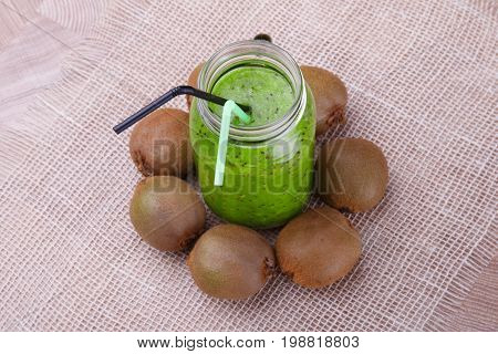 A composition of a mason jar with a green smoothie and whole kiwis on a white cloth wooden background. Organic and fresh green beverage with straws. Whole kiwis near the drink, top view.