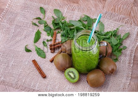 A view from above of a healthy kiwi smoothie in a mason jar with a colorful straw on a wooden background. Exotic whole and cut kiwi, cinnamon sticks and leaves near a beverage on a white cloth.