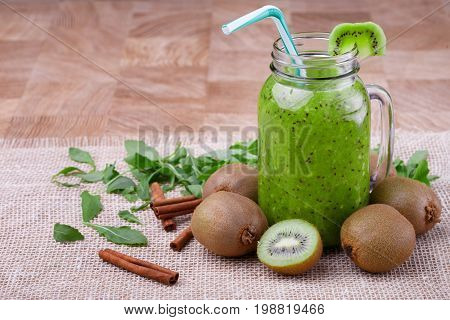A composition of a healthy kiwi smoothie in a mason jar with a colorful straw and slice of fruit on a top on a wooden background. Exotic whole and cut kiwi, cinnamon and leaves on a white cloth.