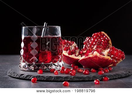 Close-up of a transparent glass of sweet pomegranate juice and a cut garnet on a round plate on a saturated black background. Summer, healthful and fruity red cocktail with straws and fresh garnet.