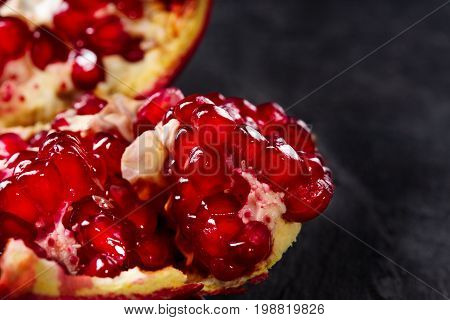 Macro photo of juicy, ripe bright red pomegranate divided into pieces on a saturated black background. Beneficially and nutritious vitamins. Useful red garnet berries for desserts or drinks.
