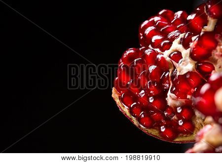 Macro photo of juicy, ripe bright red pomegranate divided into pieces on a saturated black background. Beneficially and nutritious vitamins closeup. Useful red garnet berries for desserts or drinks.
