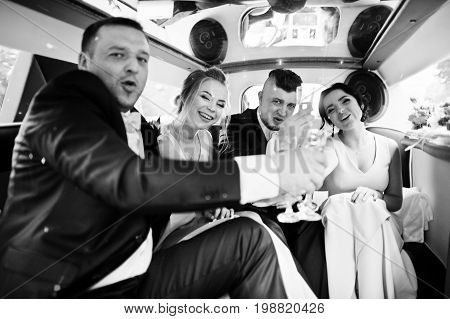 Groomsmen And Bridesmaids Drinking Champagne In The Limo. Black And White Photo.