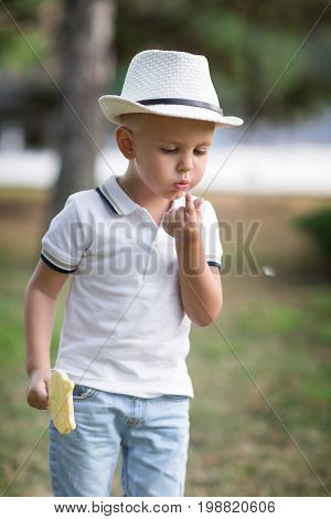 A focused little child in a white hat blowing on his finger. A casual boy with a lemon lollipop relaxing on a light park background. A portrait of a thoughtful boy looking at his finger.