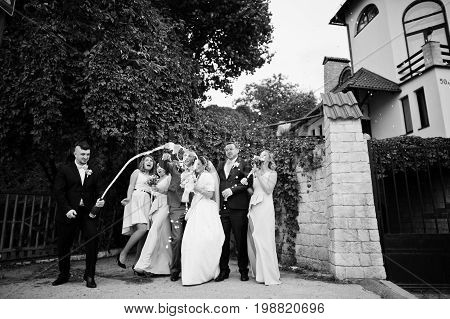 Groomsman Opening The Bottle Of Champagne And Other Groomsmen With Bridesmaids And Wedding Couple Wa