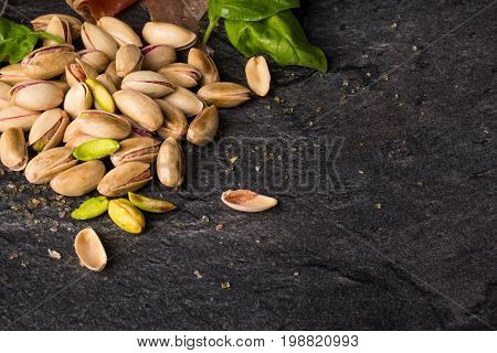 Top view of a heap of cracked pistachios and green spinach on a black background. Traditional snacks and appetizers. Salty light brown pistachio nuts for a pub or bar. Copy space.