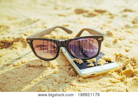 phone on the beach with sunglasses in sunny day